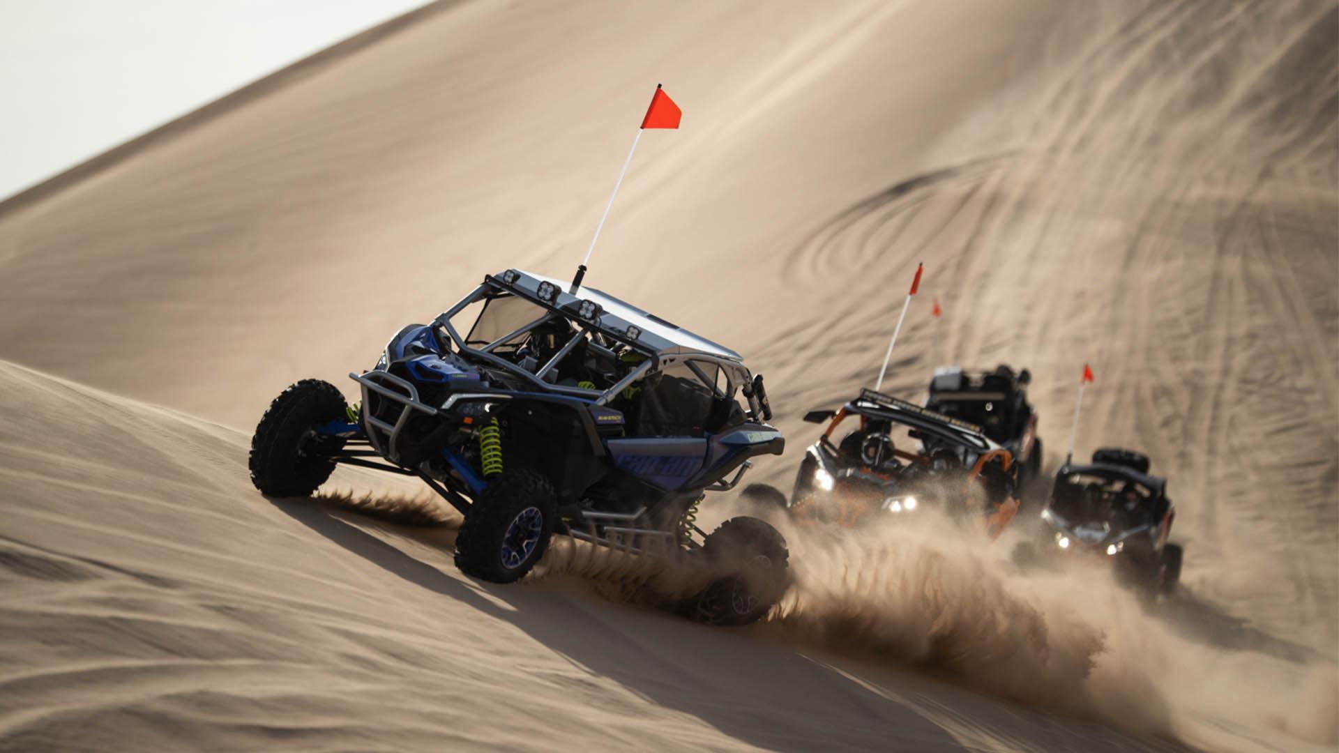 Nueva gama de Can-am Maverick X3, buggies subiendo duna sobre la arena.